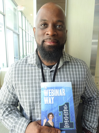 Korby Waters holds The Webinar Way book by Sherrie Rose